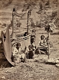 Timothy H. O'Sullivan captured some of the traditional daily life among the Navajo in this 1873 photo taken near Old Fort Defiance in New Mexico of Navajos clustered around a loom, hunting equipment and drying maize.  – Courtesy Library of Congress –