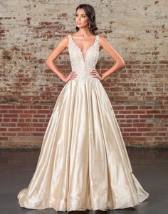 Justin Alexander signature wedding dresses style 9855 Beaded appliques over metallic lace adorn the bodice of this V-neck ball gown to the basque waistline. This royal look is completed with an illusion V-back, Silk Dupion full skirt, pockets, and a cathedral length train.