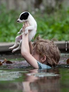A Little Boy in Serbia Battles the Floods Carrying His Puppy