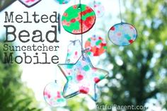How to make a colorful mobile from melted plastic bead suncatchers -- such a fun craft to do with kids! These melted bead suncatcher shapes are durable, too