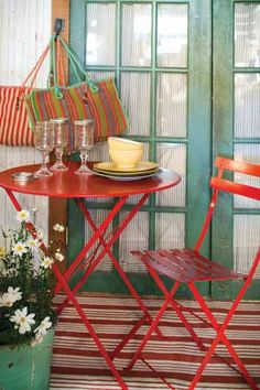 Painted door frame, colorful outdoor rug accented with bistro furniture and potted plants