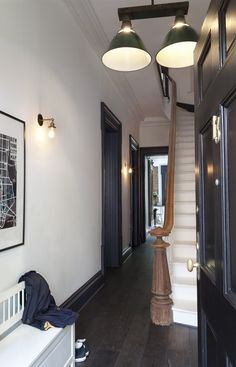 A Brooklyn Heights townhouse has been re-invented through a collaboration of an inspired client vision and a creative architectural realization with. White Hallway, White Walls, Grey Woodwork, Townhouse Interior, Brownstone Interiors, Dark Doors, Hallway Colours, Brick And Wood, Brooklyn Heights