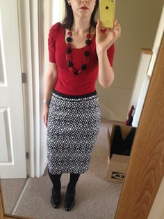 Black and white knee length skirt, red top, black and red statement necklace, black Mary Jane shoes