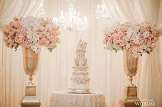 Two bountiful #floral arrangements flanked this opulent, gilded #cake setup | Photography By: AGI Studio | WedLuxe Magazine | #WedLuxe #Wedding #luxury #weddinginspiration #luxurywedding #weddingcake
