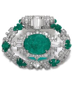 CARTIER - An Art Deco emerald and diamond brooch, circa 1935. Of openwork design, set with a carved emerald cabochon surrounded with circular-, single-cut and baguette diamonds, within a frame of garland design set with carved emeralds, circular-, single-, square-cut and baguette diamonds, signed Cartier, numbered. #Cartier #ArtDeco #brooch