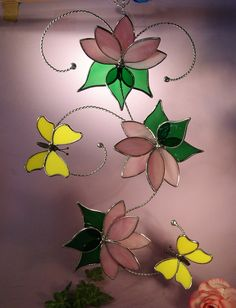 This Stained Glass Suncatcher with Butterflies and Flowers will beautify any household window or wall.    The two Butterflies are delicately balanced and flying around their favorite flowers.    Makes for a great gift for someone special or just maybe the special one is you. This is a 'One of a Kind'.    The Butterflies wings are made with a bright yellow glass, there are three Whispy Pink flowers with 15 pedals and 9 green leaves surrounding the them.    All are held together with…