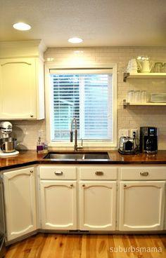 DIY painted cabinets, butcher block, and looks like subway tile backsplash! Lovely!