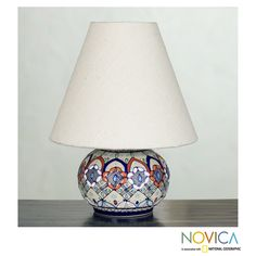Javier Servin designs a colorful trellis for the base of this spectacular lamp. Crafted of ceramic, the lamp is painted by hand creating raised textures and is complemented by a neutral cotton lampshade.