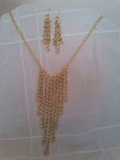 Conjunto de gargantilla caida y pendientes color dorado.
