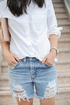 Blogger Crystalin Marie styles her Gap oxford shirt with ripped denim shorts.