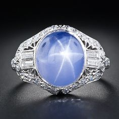 An enchanting velvety lavender-blue star sapphire, weighing 10 carats, and displaying a vivid six-pointed star, is majestically presented in a gorgeous, top notch platinum and diamond setting. This sublime and all original Art Deco jewel, circa 1925, is consummately ornamented with two pairs of shimmering straight baguette diamonds, small sparkling single-cut diamonds, decorative open work and a touch of hand engraving