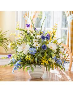 "{$tab:description} Add a touch of garden sunshine The happy color in this bountiful silk flower centerpiece renders freshness and beauty to your dining, sofa, or entry table. The wonderful combination of magnolia, larkspur, and daisy arranged with a plethora of greenery will add a touch of garden sunshine to your home decor. {$tab:DETAILS}        21"" Height x 24"" Width  White Ceramic Container - 4.75""H x 6""Diameter Ideal Sunny Kitchen or Foyer Table Arrangement&am..."
