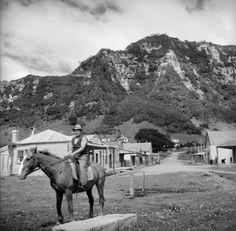 Man on a horse on the main street of Te Araroa, on the occasion of the hui for Te Moananui-a-kiwa Ngarimu. Pascoe, John Dobree, 1908-1972