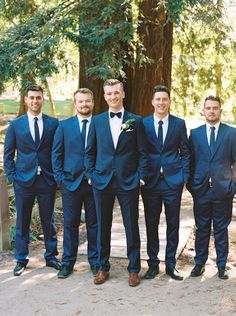 simple chic navy blue Hugo Boss suit paired with bow tie and brown leather shoes | great groom style | groom is differentiated with his bow tie and boutonniere and classic neck ties for the groomsmen | Organic Style Wedding in Sacramento
