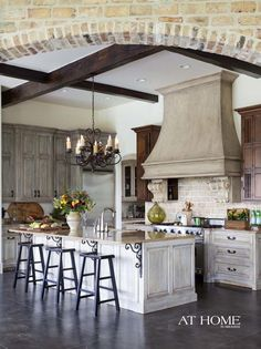 old world style, brick arch, exposed beams, patina cabinets