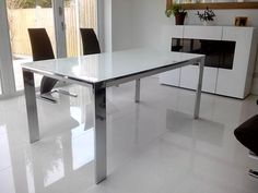 Cosmopolitan glass extendable table in white with Chrome frame and legs. Size is 165cms and 265cms fully extended. Tall sideboard is from our NAT range in matte white, NAT i511. Delivered to our client in Virginia Water, Surrey.