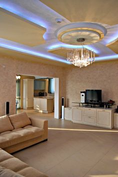Fantastic Living Room Idea with Blue Hidden Ceiling Lights Paint Color and L Shaped Creamy Sofa Completed and Small TV LCD and Romantic Pendant Lamps also White Storage Shelves