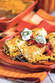 Smothered Enchiladas - Quick-Fix Suppers from the Pantry - Southernliving. Recipe: Smothered Enchiladas   Canned cream of chicken soup, canned green chiles, and a container of sour cream form a super-quick, creamy sauce to coat these beef-stuffed enchiladas. Top with salsa, sour cream, green onions, and fresh cilantro.
