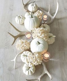 White fall center piece decorated with white pumpkins and antlers