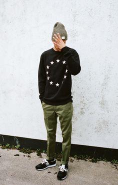 Grey beanie, star graphic black sweatshirt, skinny khakis and black trainers.