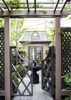 Although not necessarily this style for my house, I like the elements- fountain, glimpse of garden beyond, pergola, tall dark lattice fence with airy gate...