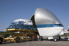 Orion service module secured to platform with open front of Super Guppy aircraft at left