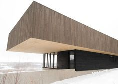 Top-heavy timber house situated in the mountain landscape of eastern Quebec.