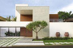 Um grande Pandanus escultural compõe o jardim da fachada juntamente com vasos em cerâmica rústica vindos de Bali