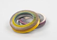 Bracelet (plastic, coated paper, elastic thread) by Nel Linssen.