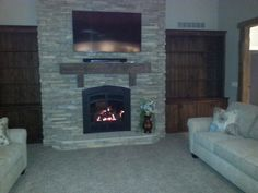 Stone fireplace with built-ins and concrete faux wood beam mantle