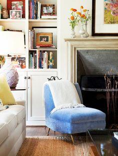 blue velvet slipper chair, lovely big fireplace, built-in bookcase, fresh flowers, black-framed art