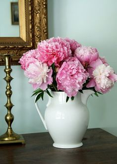 a bouquet of pink peonies in a white pitcher