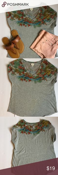 Anthropologie gray tee with floral design❤️❤️❤️❤️ Anthropologie gray tee with floral design. This tee is in great used condition with no stains or holes. It has a rounded hem at the bottom. This top is machine wash. The top is approx 24 in from top of shoulder to hem. Anthropologie Tops Tees - Short Sleeve