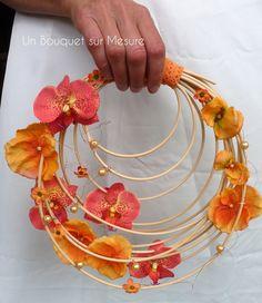 Création made in France 100% fait-main par Un Bouquet sur Mesure -- Bouquet de mariée très original et amusant avec son coté année seventy. IL est léger et se porte très facilement. Confectionné sur une base de rotin, il est agrémenté de fleuron d'orchidée venda, d'hortensia et de fleurs d'euphorbia. Le tout,relevé d'un fil cuivré et de quelques perles. La poignet et décoré de ruban dentelle orange.