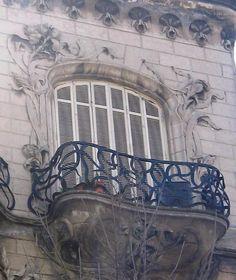 """Las mil y una curiosidades de Buenos Aires En Rivadavia 2031 se levanta la llamada """"Casa de los lirios"""", del ingeniero Eduardo Rodríguez Ortega. Es uno de los ejemplares más logrados del art nouveau en Buenos Aires. Los manojos de jacintos que envuelven el frente le otorgan un aspecto casi fantasmal, trepando por sus balcones y la totalidad de la fachada. La contención de la baranda superior, con forma de hombre barbudo, respeta las líneas libres y sueltas del art nouveau."""