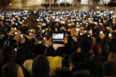 Católicos toman fotos con sus teléfonos y tabletas de la nueva elección del papa Francisco, mientras él habla desde el balcón central de la Basílica de San Pedro en el Vaticano.