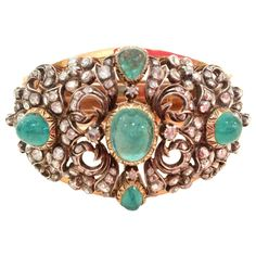 Victorian Cabochon Emerald Diamond Bracelet. Victorian cuff bracelet is fashioned from 14k yellow gold with a silver overlay to provide unusual depth. Openwork pattern is adorned with five cabochon emeralds (10 ct total weight) are surrounded by rose-cut diamonds (3.5 ct total weight). Circa 1860-1880