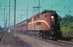 Pennsy GG-1 #4907 hustles along the Northeast Corridor at Edison, New Jersey with a northbound commuter run circa 1962.