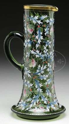 James D. Julia, Inc. -  Moser Tankard Pitcher. Large Moser tankard has flaring foot and cylindrical body with applied green glass handle. Pitcher is decorated with brightly colored enamel thistles encircling the entire body of the tankard. Lip is finished with a gilded band and the flaring foot is decorated with a line of white enamel dots