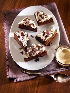 Schokoladige kleine Kuchen-Ecken mit einer Dekoration aus Sahne und Schokoladenraspeln