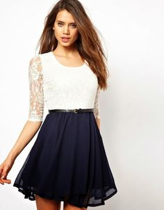 a short dress with long sleeves, top waist is white with a white lace top and black color and is wearing a black belt