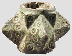 Streitkolbenkopf - Südosteuropa, 14.Jhdt. Bronze mit grünschwarzer Patina. Vierseitiger Kopf mit runder Tülle, die diamantierten Schlagflächen mit Kreisaugendekor. Gereinigter Bodenfund. Höhe 3,7 cm.