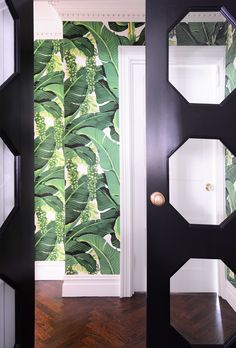 palm leaf wallpaper and black cutout doors.