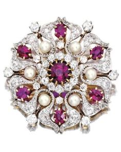 Platinum, Gold, Ruby, Diamond and Pearl Brooch, Pickslay & Co. The stylised flowerhead centring a round ruby framed by six oval-shaped rubies and six pearls, accented by old European and rose-cut diamonds, signed Pickslay & Co.; circa 1900; fitted with pendant hook. Z