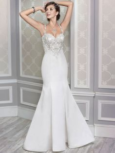 This stunning form fitting trumpet silhouette features a swarovski crystal encrusted bodice with intricate details of bead work. Paired with an illusion back panel finished with satin covered buttons with alternating crystals that continues down to the hem.