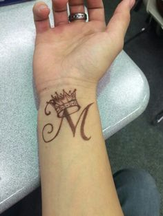 Wrist tattoo. Letter M with a crown. Crown means self control & a reminder to use power wisely