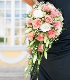 Pink roses and white lisianthus make up a very formed, traditional cascade