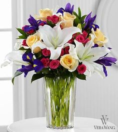 New Day Dawns Bouquet -  A colorful burst of roses and iris form a charming bouquet of spring sophistication and timeless elegance. Pale yellow roses, deep purple iris, fuchsia spray roses and white Oriental lilies are brought together to create a stunning flower bouquet.