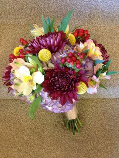 Purple can be a unique twist when added to a fall color palette as in this bridal bouquet. Purple hydrangeas act as the canvas for peach Peruvian lilies, yellow billy balls, rust and burgundy mums.  www.bloomtasticweddings.com