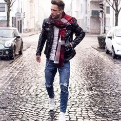 Shop this look on Lookastic: https://lookastic.co.uk/men/looks/biker-jacket-crew-neck-t-shirt-skinny-jeans/18362 — Red Plaid Scarf — White Crew-neck T-shirt — Black Leather Biker Jacket — Blue Ripped Skinny Jeans — White Low Top Sneakers